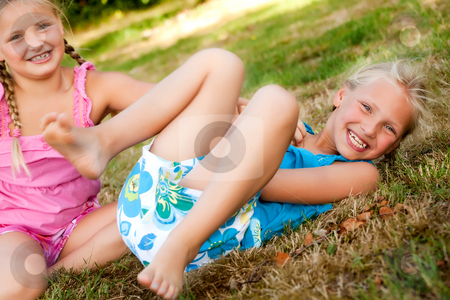 The twins are playing stock photo, Two little girls in fresh colors in the park by Frenk and Danielle Kaufmann