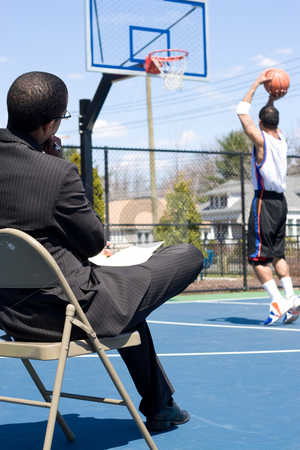Basketball Coach stock photo, A basketball coach in a business suit observing a player on the team.   He could be also be recruiter trying to scout him. by Todd Arena