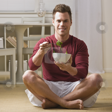 Man with bowl of salad stock photo, Attractive man smiling at camera, sitting in lotus and eating salad. Square. by Jonathan Ross