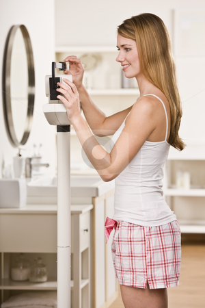 Attractive blonde on scale. stock photo, Attractive blonde woman on scale, weighing herself and smiling. Not looking at camera. Vertical by Jonathan Ross