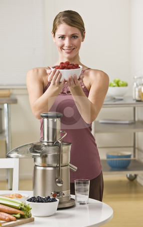 Attractive blonde with berries and juicer stock photo, Attractive blonde woman holding bowl of berries and smiling at camera. Vertical by Jonathan Ross