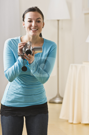 Attractive woman with video camera. stock photo, Attractive brunette woman with video camera, smiling at the camera. Vertical. by Jonathan Ross