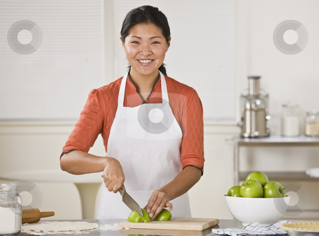 Asian woman slicing apples. stock photo, Smiling Asian woman standing at counter and slicing apples.Horizontal by Jonathan Ross