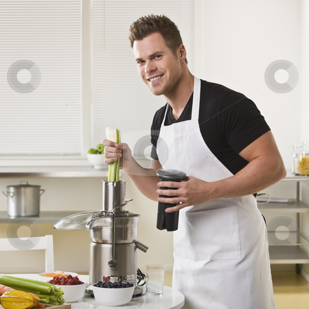 Attractive male with juicer. stock photo, Attractive male with juicer, holding celery and smiling at camera. Square. by Jonathan Ross