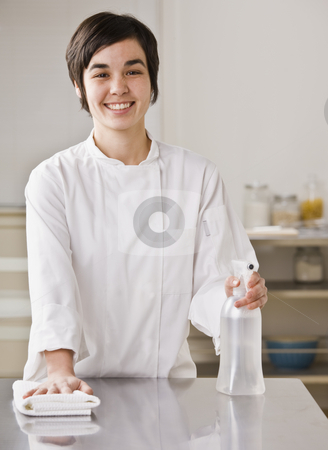 Woman Cleaning Counter stock photo, A woman is cleaning the counter in a kitchen.  She is smiling at the camera.  Vertically framed shot. by Jonathan Ross