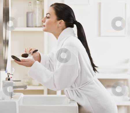 Woman Putting on Makeup stock photo, A young woman is standing in front of the bathroom mirror and putting on makeup.  Horizontally framed shot. by Jonathan Ross