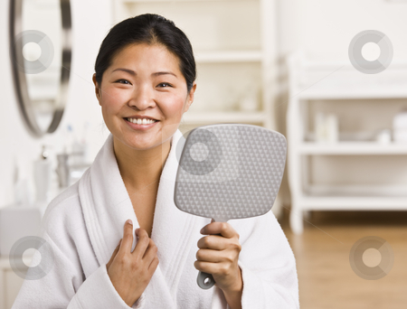 Asian woman holding mirror. stock photo, Asian woman holding mirror, wearing robe and smiling at camera.Horizontal. by Jonathan Ross