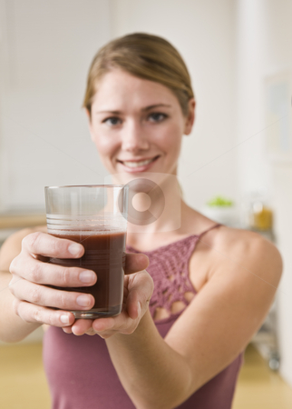 Woman Holding Glass of Juice stock photo, A young woman is holding up a glass of juice and smiling at the camera.  Vertically framed shot. by Jonathan Ross
