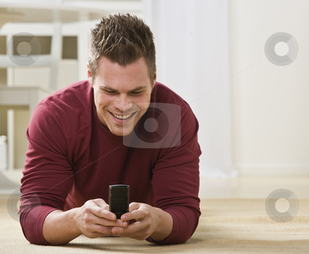 Attractive male with cell phone. stock photo, Attractive male smiling and lying on the floor while looking at cell phone. Horizontal by Jonathan Ross
