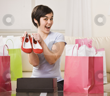 Woman Holding Red Shoes stock photo, A young woman is surrounded by shopping bags and is holding out a pair of shoes.  She is smiling at the camera.  Square framed shot. by Jonathan Ross