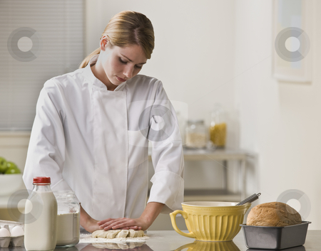 Woman Making Pie stock photo, A woman is making a pie in her kitchen.  She is looking away from the camera. by Jonathan Ross