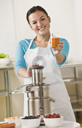 Woman Holding Juice stock photo, A woman is standing in her kitchen holding out a cup of juice.  She is smiling at the camera.  Vertically framed shot. by Jonathan Ross