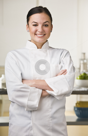 Attractive female chef. stock photo, Attractive brunette, female chef smiling at the camera with her arms crossed. Vertical by Jonathan Ross