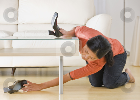 Asian woman reaching for shoe. stock photo, Asian woman kneeling on floor and reaching for shoe under coffee table. Horizontal. by Jonathan Ross