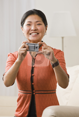 Woman Taking Picture stock photo, A woman is holding a camera in her hands.  She is smiling at the camera.  Vertically framed shot. by Jonathan Ross