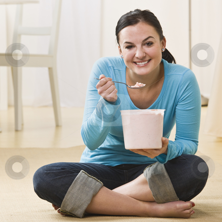 Attractive woman eating ice cream. stock photo, Attractive woman sitting on floor with crossed legs and eating ice cream. Square by Jonathan Ross