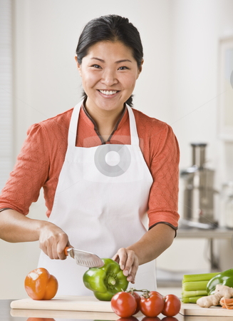 Woman Slicing Produce stock photo, A woman is slicing produce in her kitchen.  She is smiling at the camera.  Vertically framed shot. by Jonathan Ross