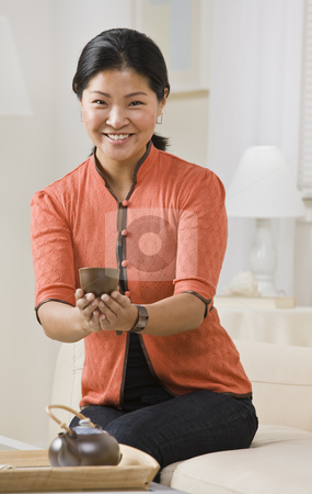 Asian woman serving tea. stock photo, Asian woman serving tea smiling at camera. Serving tea in Asian cup with small tea pot on table. Vertical by Jonathan Ross