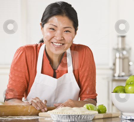 Asian woman making pie. stock photo, Asian woman rolling dough, making pie, smiling at camera with flour on her face. Square. by Jonathan Ross