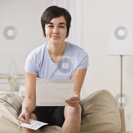 Smirking woman with paper. stock photo, Smirking brunette woman holding paper and facing the camera. Square. by Jonathan Ross