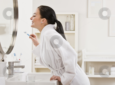 Woman Brushing Teeth stock photo, A young woman is standing in front of the bathroom mirror and brushing her teeth.  Horizontally framed shot. by Jonathan Ross