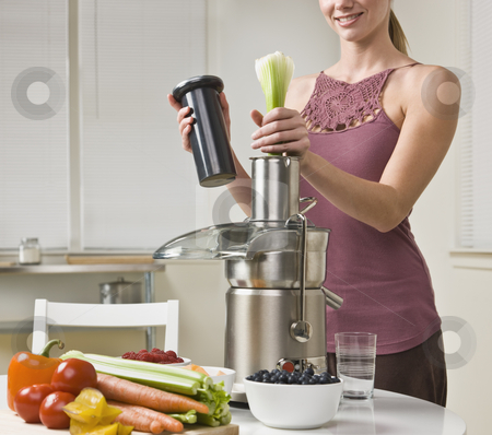 Attractive woman using juicer stock photo, Attractive woman with juicer machine, adding celery and smiling. Horizontal. by Jonathan Ross