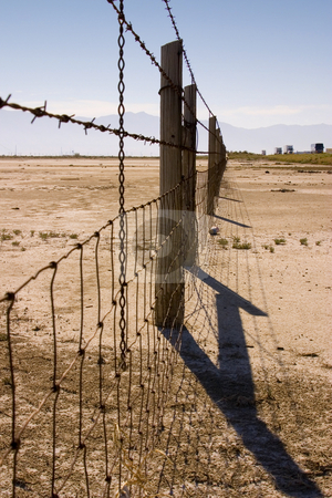 Fence Under Clear Skies stock photo, Fence in the Sale Lake in Summer in Utah with Clear Blue Skies by Mehmet Dilsiz