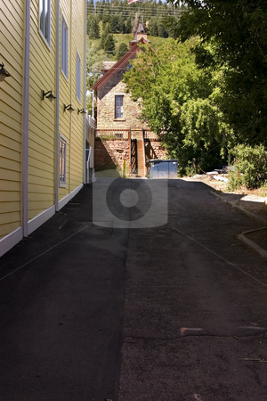 Yellow Sidings of a Building in an Alley stock photo, Side Alley in Park City, Utah - a Building Along the Side with Yellow Siding and Lamps by Mehmet Dilsiz