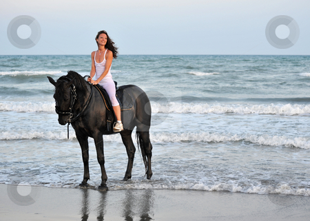 Riding girl on a beach stock photo, Young woman an her black stallion in the sea by Bonzami Emmanuelle