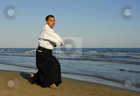 Aikido on the beach stock photo, A young man are training in Aikido on the beach by Bonzami Emmanuelle