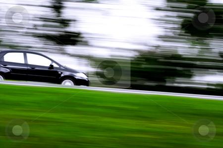 Rushing away going downtown stock photo, A black car rushing away on a countryside highway by R. Eko Bintoro