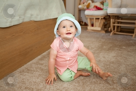 Green hat stock photo, Caucasian baby girl in green hat playing on a floor. by Mariusz Jurgielewicz