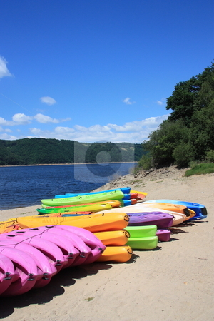 Kayaks stock photo, A row of colourful kayaks on a beach with the blue water and blue sky behind. by Gozzoli
