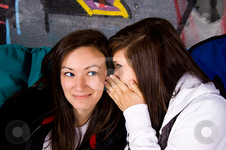 Teenagers - Whispering a Secret stock photo, One Teenage Whisper Something into the Ear of her Friend by Mehmet Dilsiz