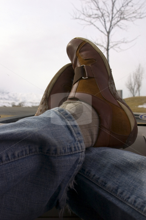 Feet crossed over on the Dashboard Relaxing stock photo, Feet crossed over on the dashboard relaxing during lunch with trees on the background by Mehmet Dilsiz