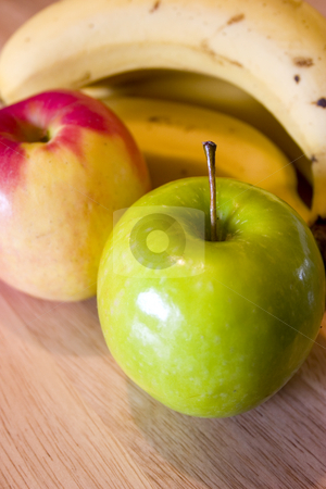 Apples and Bananas stock photo, Close up on Green, Red Apples and a Banana with the focus on the stem of the Green Apple by Mehmet Dilsiz