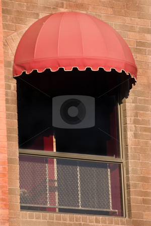 Brick Wall and A Window with Red Awning stock photo, Close up on a Red Awning with brick walls by Mehmet Dilsiz