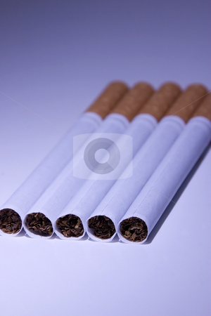 Isolated Cigarettes Under Blue Light stock photo, Isolated Unsmoked Cigarettes Under Blue Light by Mehmet Dilsiz