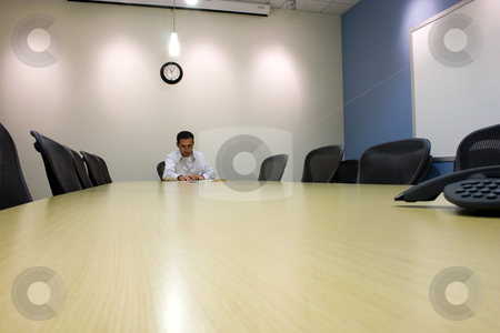 Businessman in a Conference Room  stock photo, Businessman looking over his galsses in a Conference Room by Mehmet Dilsiz
