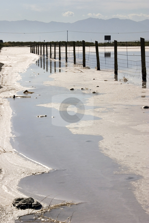 Vertical shot of a Fence in Salt Lake stock photo, Fence in the Salt Lake , Utah with Clear Blue Skies and by Mehmet Dilsiz