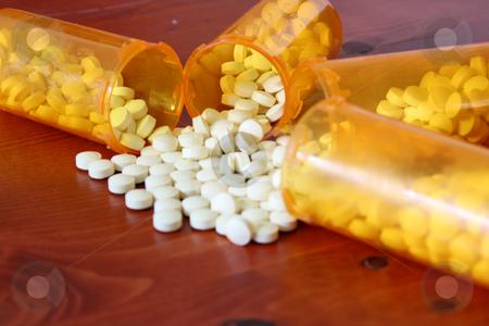 Bottles of Medicine stock photo, Medicine spilling out of bottles by Mehmet Dilsiz