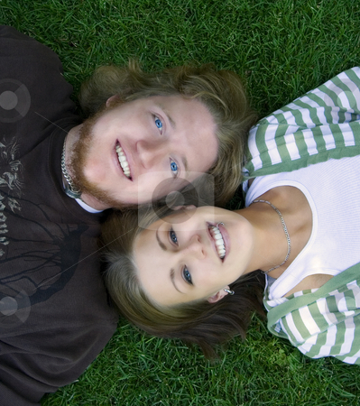 Young couple looking at the camera laying down stock photo, Young Married Couple laying down looking up to the camera by Mehmet Dilsiz