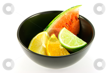 Citrus Fruit and Watermelon stock photo, Wedges of lemon, lime and orange in a small black dish with a slice of juicy watermelon on a white background by Keith Wilson