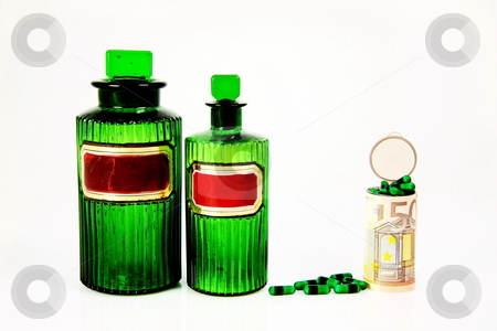 Rising Medical Costs Euros stock photo, A conceptual image of rising medical costs with two green antique pharmacy bottles, green capsules and a euro banknote wrapped around a prescription bottle filled with capsules, isolated on white. by Gozzoli