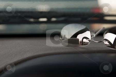 Sunglasses on the deck stock photo, Steering wheel reflection on the sunglasses on the deck by Mehmet Dilsiz