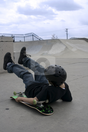 Skateboarding Kid on the Ground stock photo, Close up to a Boy Who Fell with a Skateboard by Mehmet Dilsiz