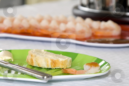 Close up on sliced bread on a plate stock photo, Close up on a sliced bread with blurred shrimps on the background by Mehmet Dilsiz