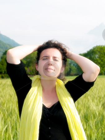Woman in barley field stock photo, Photo of an attractive french woman wearing a yellow scarf standing in a green barley field orton processed by Laurent Dambies