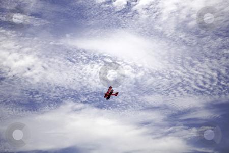 Red Biplane stock photo, Vintage red biplane flies beneath fair-weather clouds by Bart Everett
