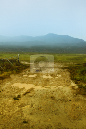 Dirt Road to the Mountains stock photo, Dirt Road to the Mountains in a foggy weather by Mehmet Dilsiz